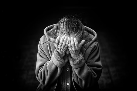 grayscale photo of person in button-up hooded jacket putting his hands in his eyes