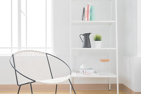 white armchair with gray steel frame near white wooden 3-layer shelf