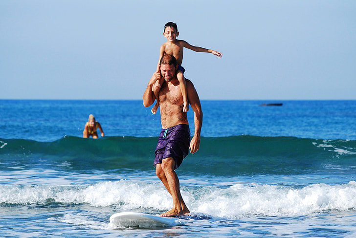 man carrying his son while riding on a white surfing board on a beach