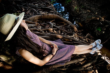 woman wearing gray dress lying on roots of trees
