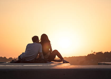 photo of man and woman sitting on sea shore during sunset