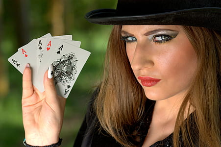 woman holding five Ace cards