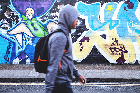 A man with a hooded-top and rucksack walks past the graffiti-covered streets of Shoreditch in East London