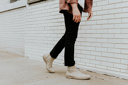 person with black pants and white shoes