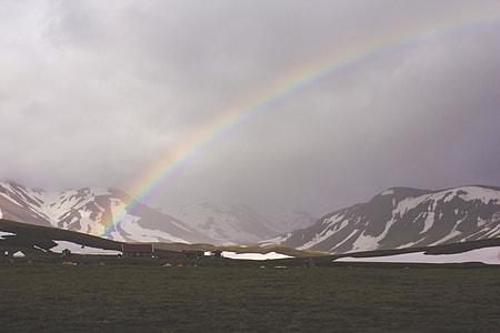 black mountains under the rainbow