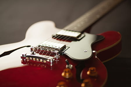 shallow focus photo of red telecaster electric guitar