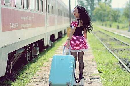 woman wearing red, white, and black polka-dot dress pulling teal luggage