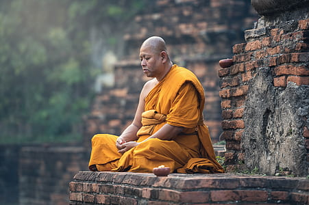 meditating monk on brown brick wall