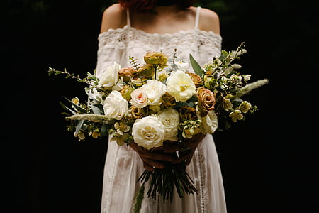 photo of woman holding bouquet of white petaled flowers