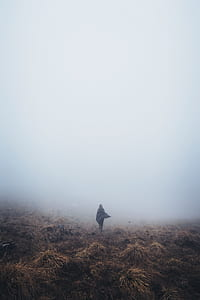 person wearing cape standing on brown ground soil under fog