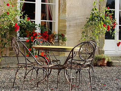 round black-and-brown metal bistro table set near the garden
