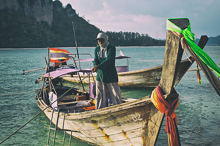 Shot of a longtail boat and man. Image captured on Tup Island, Krabi, Thailand