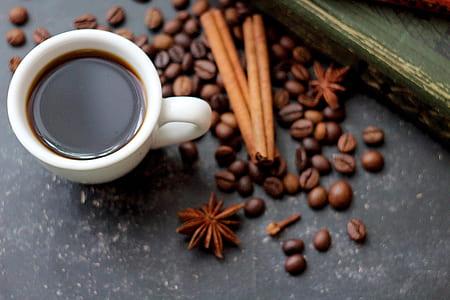 white ceramic coffee mug beside coffee beads