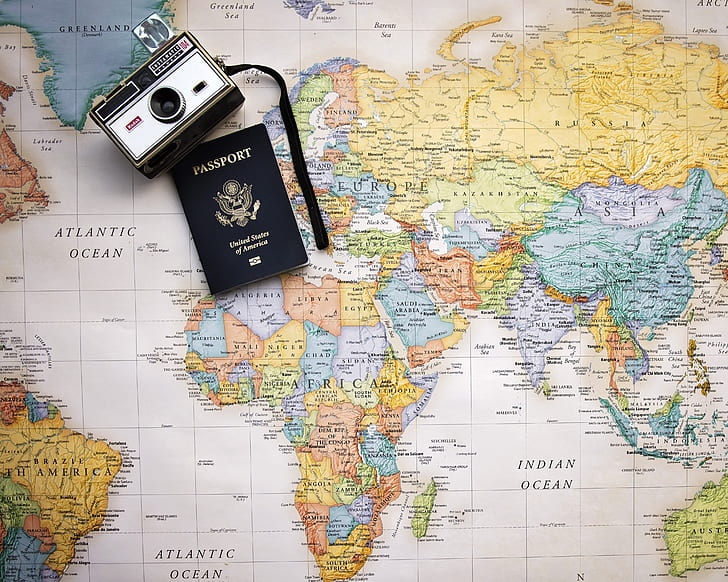 vintage grey and black camera near passport on world map