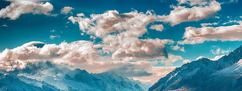 mountain range under partially cloudy skies