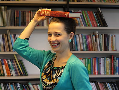 woman placing book on top of her head while smiling