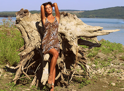 woman wearing brown and white leopard print sleeveless mini dress posing on brown log