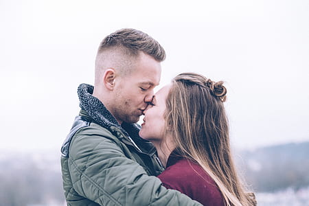 man wearing green jacket kiss her wife on nose photography