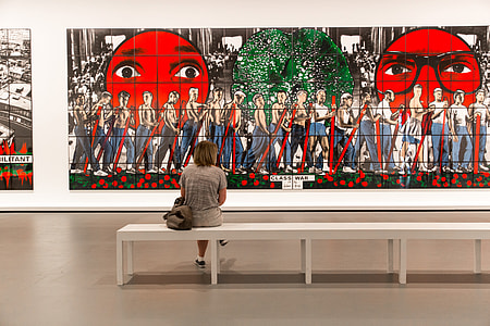 A woman sits in a modern art gallery in Paris, France
