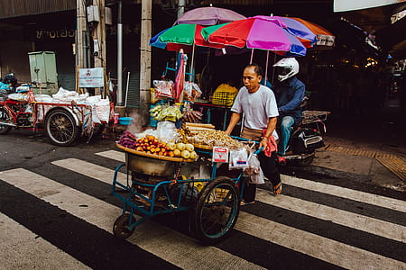 photo of man pushing cart with full of vegetables
