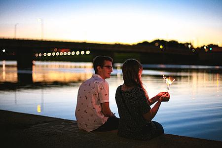 man and woman sitting beside river near bridge during sunset