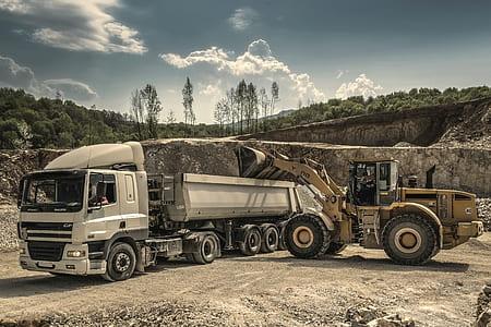 Front Load Loader Beside White Dump Truck