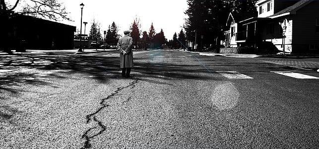 grayscale photography of man wearing overcoat standing on road