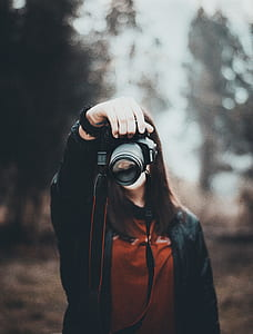 woman in red top holding DSLR camera