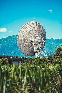 selective focus photography of parabolic antenna and mountain range view