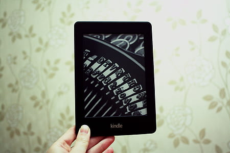 person holding black Kindle tablet