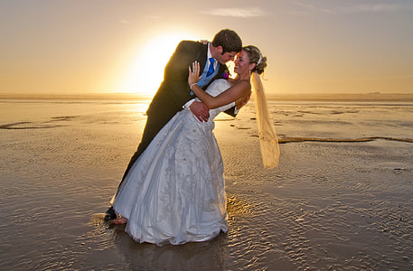 man and woman wearing wedding dresses standing on body of water