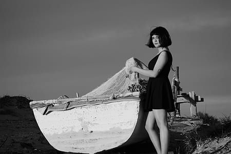 grayscale photo of woman beside boat