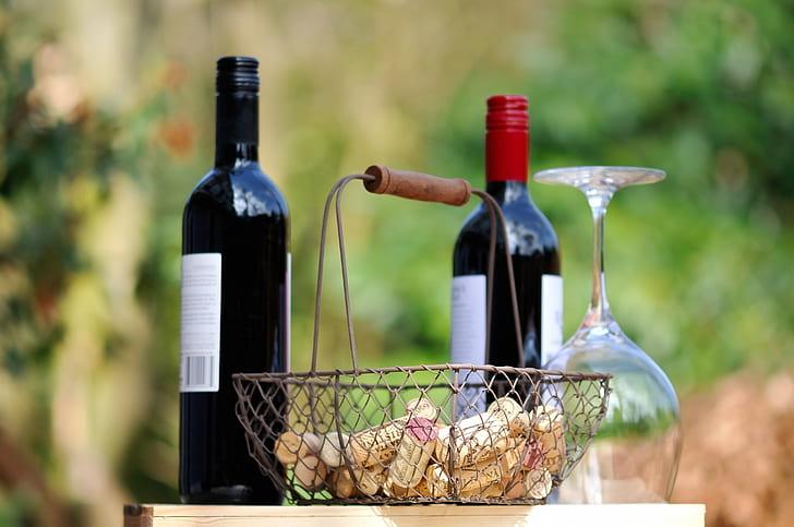 two wine bottles near gray metal basket