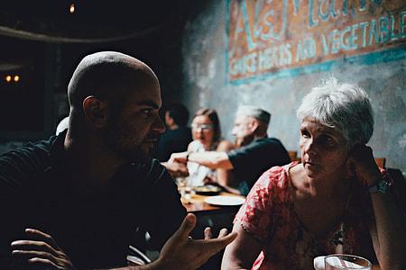 man wearing black shirt talking to woman