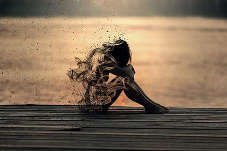 silhouette photo of woman sitting near dock