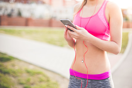 Fitness Girl Listening to Streaming Music on Her Phone