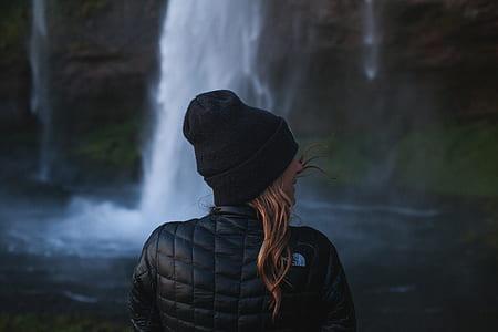 woman in black knit cap standing in front waterfalls