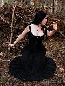 woman wearing black sleeveless dress on forest