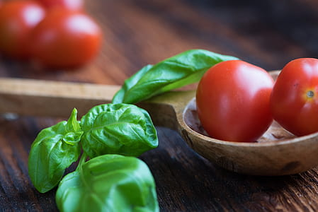 tomatoes and green leaves on top of brown wooden table