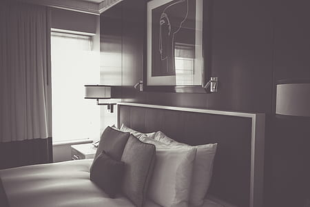 grayscale photo of bed and photo frame