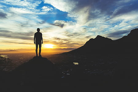 silhouette photo of a man standing of cliff