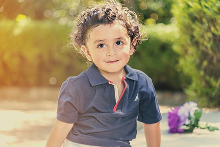selective photo of toddler's in gray polo shirt