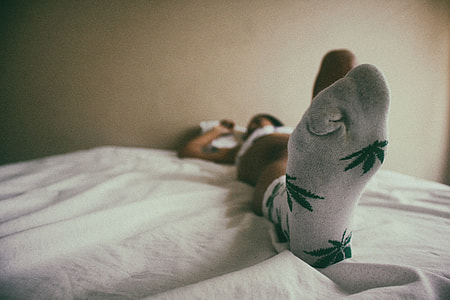 A woman lying in house bedroom wearing socks on her feet