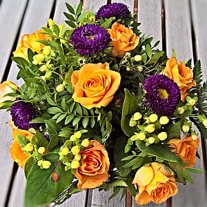 yellow, purple, and green flower center piece on brown wooden surface