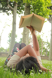 woman lying on grass field reading book beside green tree