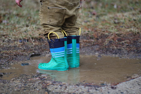 person with brown denim pants tea-and-black rain boots on body of water during daytime