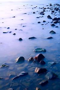 black rocks on body of water at daytime