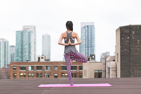 woman standing on pink yoga mat photography