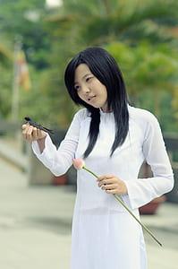 woman wearing white long-sleeved shirt holding black bird and pink tulip flower during daytime