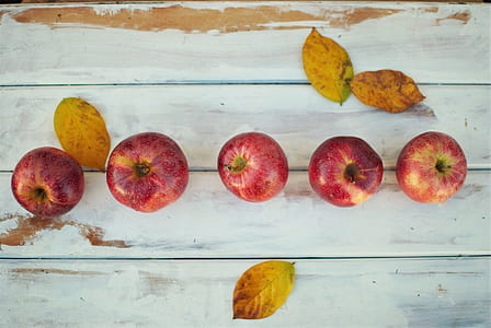 five red apple fruits on white wood pallet